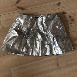 Kort kjol i silver med volang fram, från Zara. Dragkedja i sidan. Använd en gång.