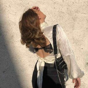 En silkes blus i cremevit / beige, öppen rygg och knytning där bak, hög hals och vida ärmar. Sjukt snygg men kommer tyvärr inte till användning🥰