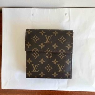En fejk Louis Vuitton som utfällbar miniväska! Perfekt på krogen eller att använda som resefack där du kan förvara pass, kort, biljetter, mynt m.m. Finns även öglor så du kan fästa kedja eller smalare rem till.   Frakt ingår i priset!