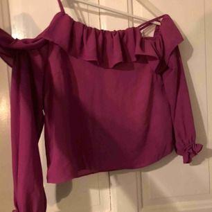 Mörk-rosa blus med volang upptill