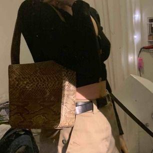Skitball handväska i fake-ormskinn!! Kort och ganska tjockt band som passar perifer att ha över axeln för en 90-tals look;)