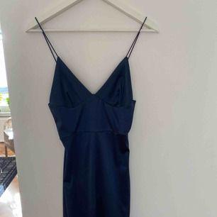 Mörkblå sidenklänning med smala axelband. Väldigt stretchigt tyg. Knä-längd. Aldrig använd.