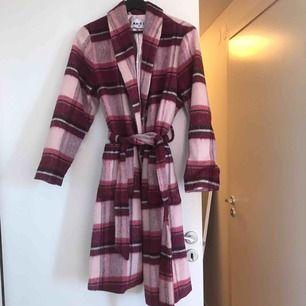 En nästintill oanvänd kappa från na-kd. Endast använd vid 3 tillfällen.  Kappa med knyte i midjan och knappar