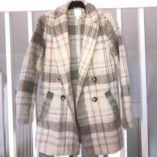 Säljer den populära beige rutiga kappan ifrån H&m. Slutsåld, passar XS/S. Frakt står köparen för
