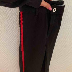 Svarta jeans med cool röd stripe längs benen. Använda ett fåtal gånger. Högmidjade och slimfit. Köpta från Bershka. Frakt ingår ej och fler bilder kan skickas vid intresse.