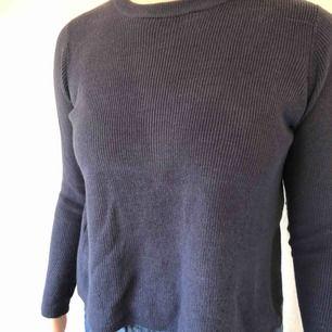 Stickad tröja från Mango i mörkblått med öppning i ryggen. Färgen illustreras bäst på närbilden. Knappt använd. Frakt tillkommer.