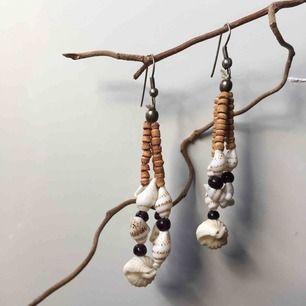 Handgjorda örhängen av snäckor och pärlor. Kan mäta mått vid intresse. Fri frakt samt spårbar.