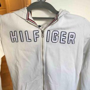Söt Tommy hoodie, saknar dock banden i luvan men kan sättas dit nya. Väl använd men i gott skick :) köparen står för frakten.