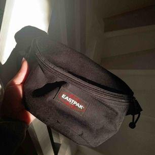 Svart magväska från Eastpak.  Knappt använd och är i superskick! Köpt för 299 kr.  Stängs med spänne. Mått: 16.5 x 23 x 8.5 🖤🖤🖤