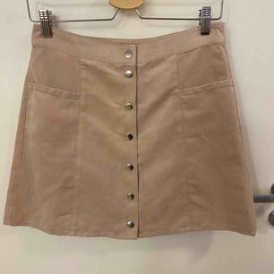 Gammalrosa kjol med knappar som öppning. Finns 2 främre fickor. Lent o mjukt tyg, använd ett fåtal gånger.