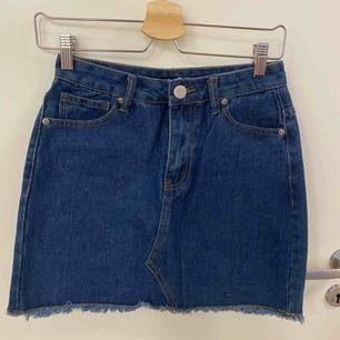 Jeans kjol med hällor upptill, fickor både fram och bak, fransar längst ner samt knapp o dragkedja som öppning. Aldrig använd