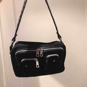 """Väska från NuNoo i manchester som heter """"Ellie corduroy"""" som är köpt från Nelly för 899kr. Mycket rymlig väska med flera fack! Säljer då jag har många väskor. Mycket fint skick, bara lite skavt på silvriga """"brickan"""" på dragkedjan."""