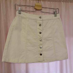 Vit jeans kjol med knappar som öppning. Aldrig använd