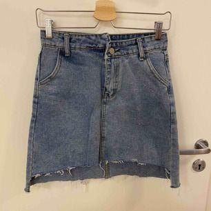 Hip jeanskjol med fickor både fram o baktill. Dragkedja samt knapp som öppning. Kjolen är lite längre baktill än framdelen. Köpt på utländsk sida så står L men är SMALL