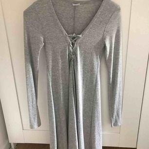 Grå klänning från Gina Tricot i storlek XS, men passar även S. Knytning vid brösten. Aldrig använd!