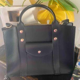 En mellanstor svart läder väska.  Går att använda den som crossbody väska och overshoulder väska! Säljer pga att den bara legat hemma utan att jag använt den.  Nypris: 955kr
