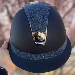Blå miss shield ridhjälm med polo skärm och swarovski crystal fabric top och band.    Stl. M, 55M ~ 58M   Använd ett fåtal gånger på tävling, som ny!   Köpt för 8000 kr