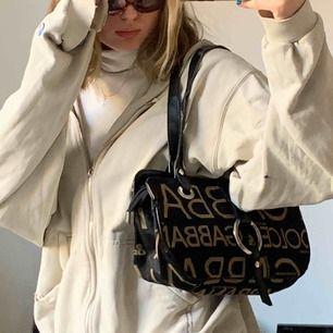 Svart och guldig väska med silverdetaljer från Dolce & Gabbana. OK skick. Kort väskband, sitter snyggt, passar det mesta och rymmer mycket.