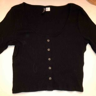 Svart tröja med knappar  Djup urringning  Nypris 200kr  Ej använd