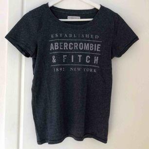 T-shirt från Abercrombie & Fitch med fadad text. Fint skick. Storlek S men passar M.