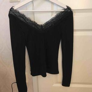 Svart långärmad tröja i offshoulder i spets. Sitter sjukt fint på då man får en kvinnlig överkropp. Frakt tillkommer