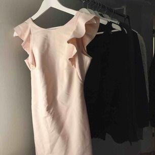 En rosa klänning med öppen rygg och volanger Använd en gång så fint skick Skrynklig men går att stryka