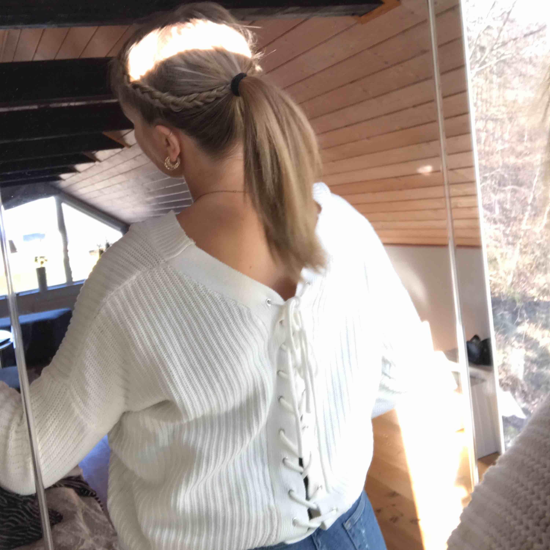 Populär stickad tröja från Nelly, snörning bak i ryggen. Stickat.