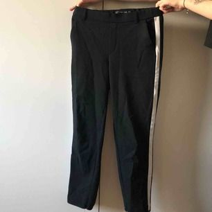 Byxor som kan kläs upp men även användas som mjukis. En vit rand på vardera ben.
