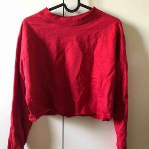 Röd långsemester tröja. Croppad vid midjan. Knappt använd.