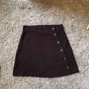 Superfin svart kjol med fina detaljer framtill, frakt är inkluderat i priset!
