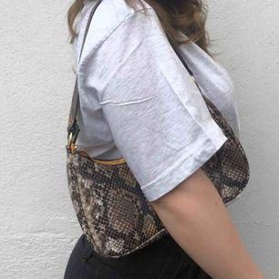 En snygg shoulderbag med ormmönster, i nyskick