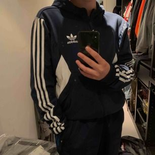 Riktigt snygg och i otroligt bra skick. En marinblå adidas hoodie med zip och luva. Fick denna för ca 1 år sedan men knappt använt den! Hoppas den kan hitta ett föralltid hem hos dig