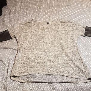 De här en stickad tröja med ganska korta armar som är gjort med fake skin. Skinet är svart.