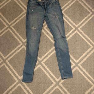 Tighta jeans med låg midja från Hollister. Små slitningar på knän och lår.