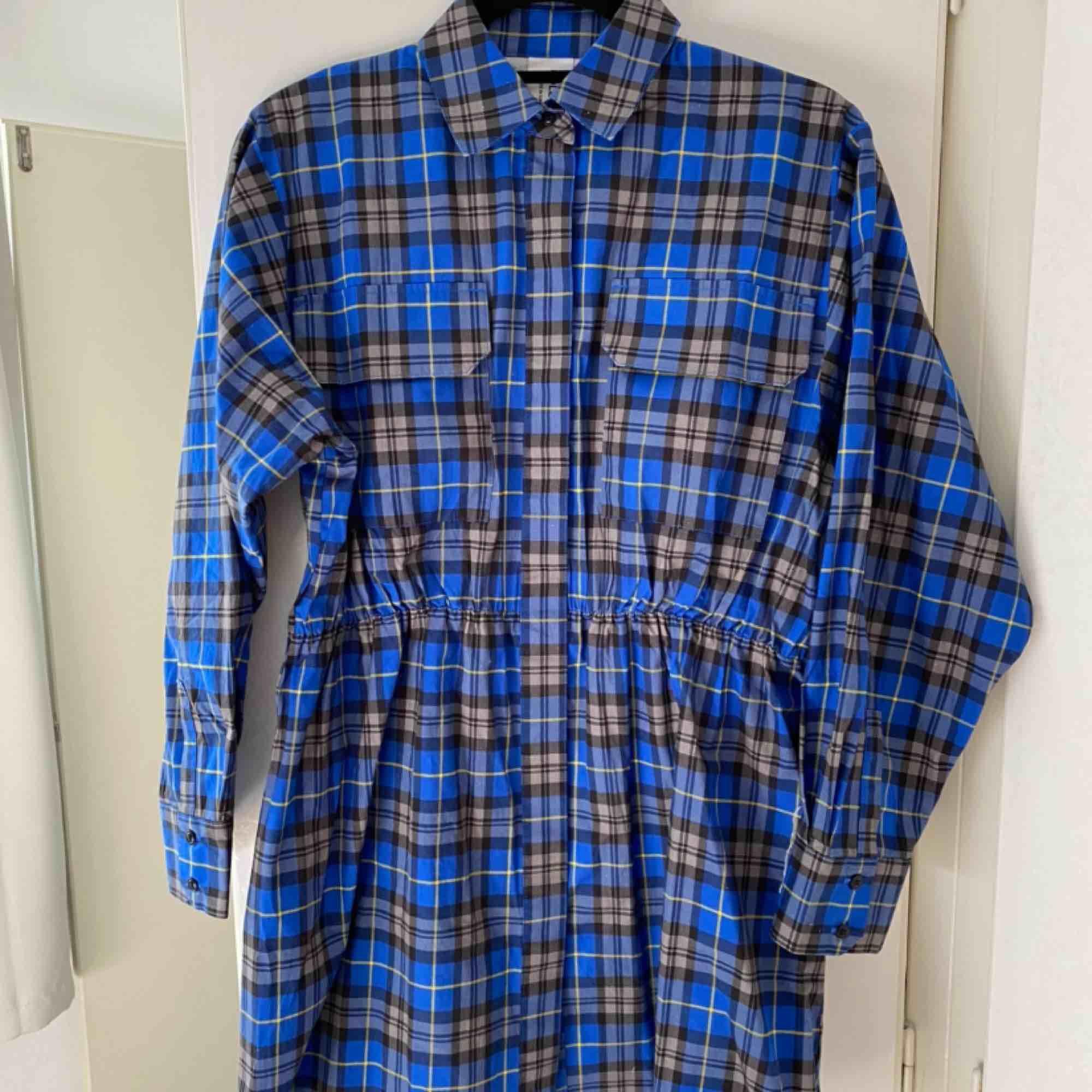 Rutig klänning med tillhörande skärp men antagbara band för axlarna. Aldrig använd. Köpt för 480kr för ca 2 månader sedan. Vid frakt står köparen för fraktkostnaden.. Klänningar.