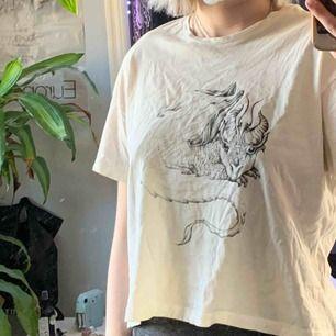 Säljer denna t-shirt med ascoolt drakliknande tryck från Weekday. Den går till naveln och är av jättemjukt material💞köpare står för frakt