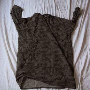 Tunn tröja med 3/4 armar som har en lite längre form. Kan troligen användas som en lite kortare klänning om man vill bära den så.