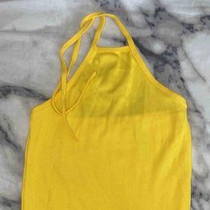 En crop top som är gul som man knyter där bak