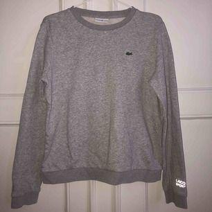 En långärmad grå tröja med reflexdetalj från Lacoste sport! Köpt för unjefär 2 år sedan men knappt använd sen dess så i väldigt bra skick!