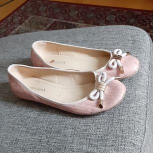 Stilrena ballerinas i dämpad rosa färg med gulddetalj. Fint skick använda ett fåtal gånger. Köpare betalar frakt.