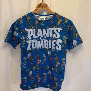 Plants vs Zombies t-shirt. Storlek S i mycket gott skick. Kan hämtas i Uppsala eller skickas mot fraktkostnad.