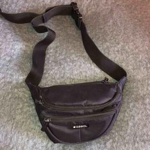 En liten magväska jag köpte i Grekland i One Size från märket Gabol! Väskan har 3 fack och är väldigt bra för utekvällar då varje fack fyller sitt (ett till mobilen, ett till plånboken osv). Har en liten repa på märket. Köpare står för frakt