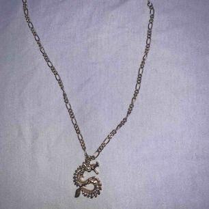 Säljer dehär guldhalsbandet med en drake på från giba tricot 💕 köpare står för frakt