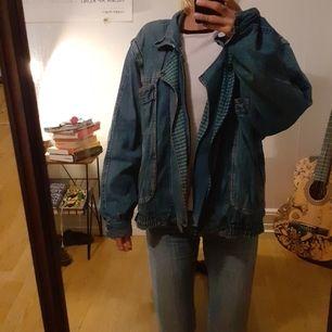 Blå jeansjacka med dragkedja samt dragkedje-avtagbara ärmar så att det istället blir en väst. Rutigt mönstrad insida.  2 Bröstfickor, 2 sidofickor och 2 innerfickor.