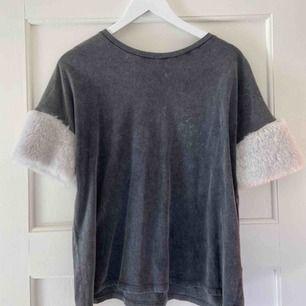Säljer en snygg gråvit t-shirt med pälsärmar (inte äkta päls)! Från Bershka i storlek XS!