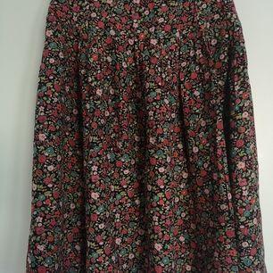 Blommig knälång kjol med bredd runt midjan, superfint på och passar med allt! Kommer inte till användning längre. Storlek 38