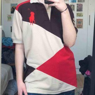 Röd, brun och beige polotröja med krage. Loose fit och lång i längden. Broderat polomärke.