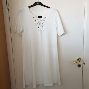 Vit luftig klänning, går halvägs ner på låren med snygg snörad urringning. Helt oanvänd och hållbart material, sitter som en S, passar bra med bälte.  Frakt tillkommer