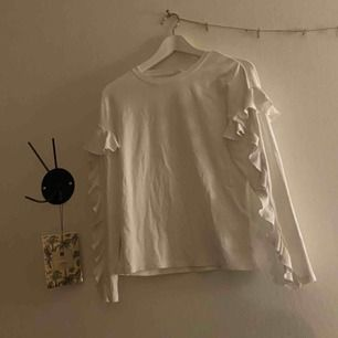 En fin vit långärmad volang tröja från hm. Kommer ej till användning. Köparen står även för frakt:)