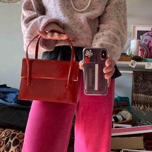 Fett söt liten röd väska i ett slags lack-material✨ Bra innerfack så går att ha både mobil, plånbok, glajjor mm. Fick av en gammal släkting så skulle gissa på tidigt 90-tal!   Möts upp på Värmdö eller Stockholm C. Fraktar också!